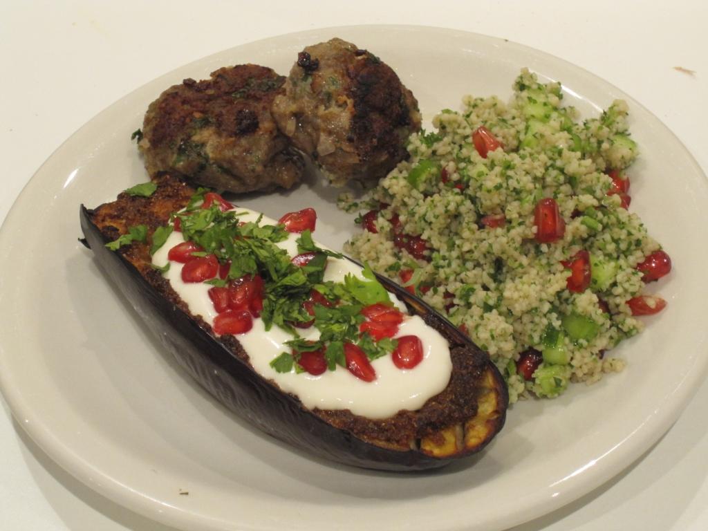 Geroosterde aubergine met tahinsaus, geserveerd met köfte en tabouleh