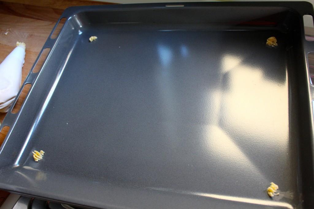 Dotjes deeg op bakplaat spuiten om bakpapier vast te plakken
