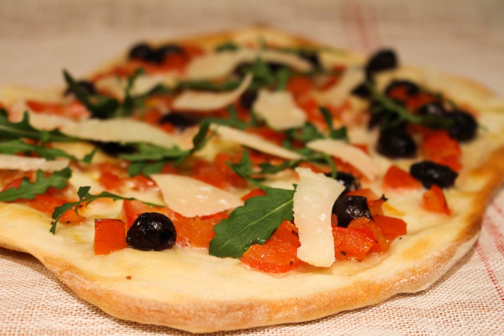 Pizza met tomaat, olijven en rucola