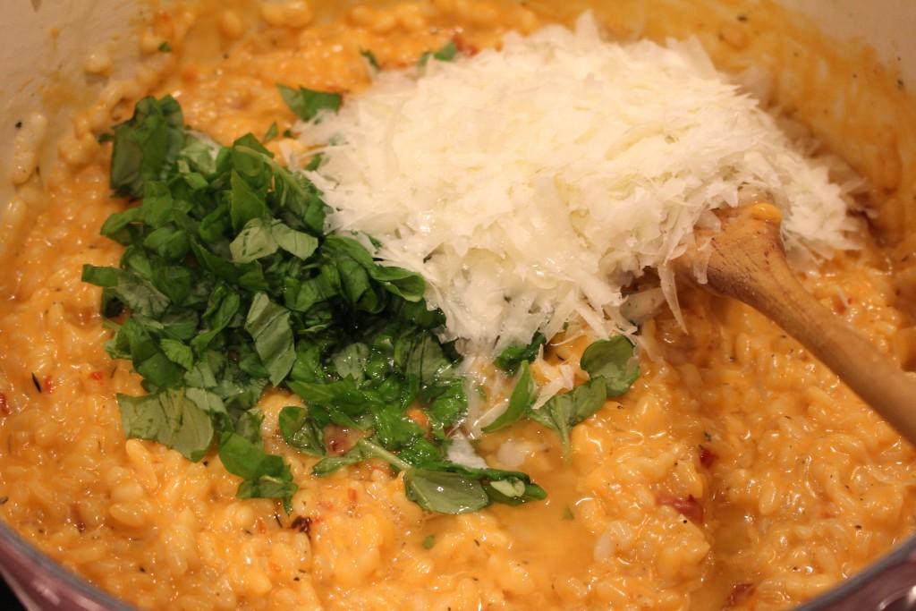 Pecorino en basilicum door de risotto roeren