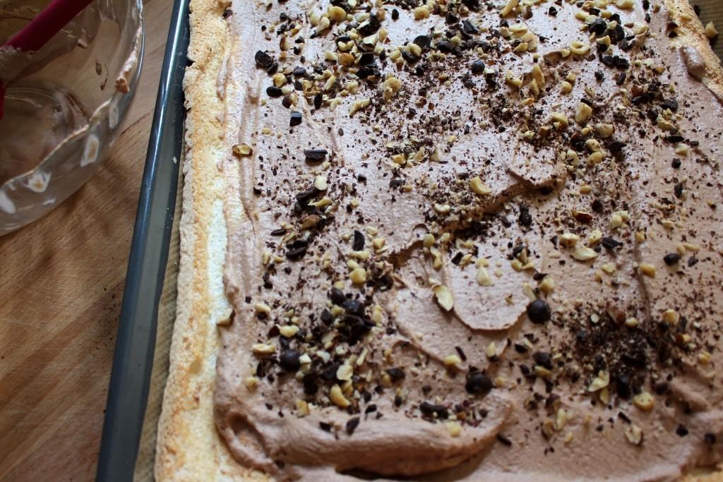 Chocoladeroom, hazelnoten en chocolade over de merengue verdelen