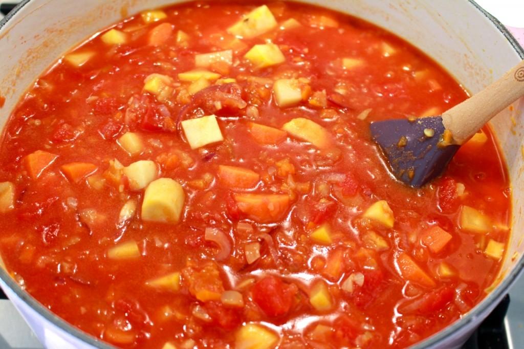 Tomaten, bouillon en harissa toevoegen