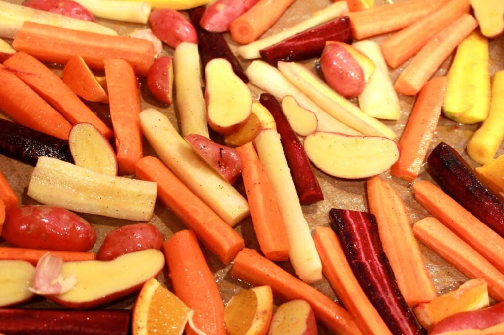 Wortels, krieltjes, look en sinaasappel over bakplaat verdelen